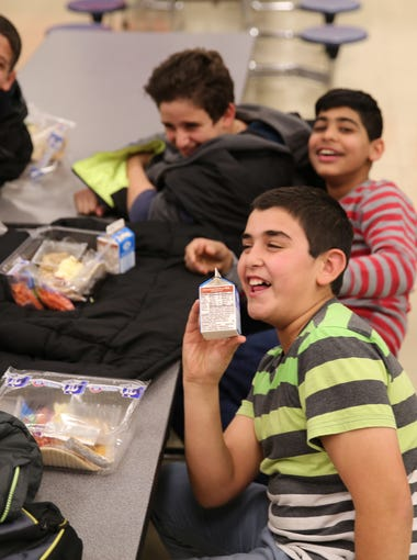 Abdulbaset Al Tybawi, 13, jokes with friends in the cafeteria at Jefferson County Public Schools' ESL Newcomer Academy.