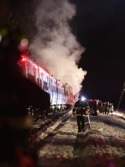 Firefighters work at the scene of a train vs car accident