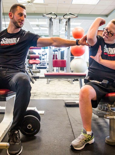 Parker Seward, 13, flexes his muscles for personal trainer Sammy Callari at his community gym in North Naples on Thursday, Aug. 10, 2017. The pair has been working out together for a year and a half and have developed a brother-like relationship. Callari works to spread awareness about the abilities, not disabilities, of those with Down syndrome.