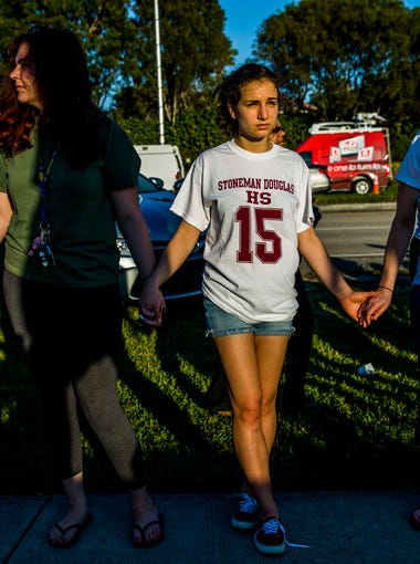 Community members hold hands and surrounding a memorial outside of Marjory Stoneman Douglas High School in Parkland, Fla. on Sunday, Feb. 18, 2018 in response to a shooting at the High School on Wednesday that took 17 lives. Today was the first day the public was allowed to visit the perimeter of the school since the shooting.
