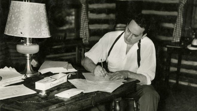Thomas Wolfe writes at his desk in the Oteen cabin to which he retreated in the summer of 1937.