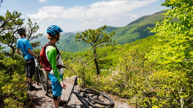 Mountain bikers take a moment to take in the mountain views on one of the trails in Old Fort.