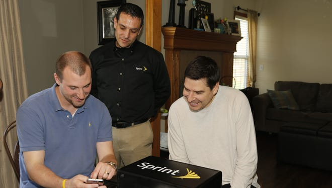 From left, customer Andrew Karle receives a new phone at his home from Sprint CEO Marcelo Claure and representative Charles Lobosco as Sprint debuts a new service called Direct 2 You on April 10, 2015, in Greenwood, Mo.