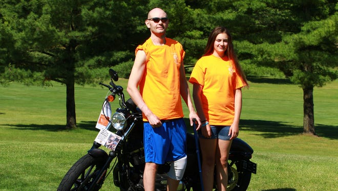 Scott Truran stands with his daughter, Amanda Truran, at a golf tournament fundraiser for his health care at Riverside Golf Club.