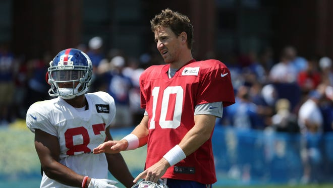 New York Giants quarterback Eli Manning, right, talks to teammates during practice at the NFL football teams training camp in East Rutherford, N.J. on Tuesday.