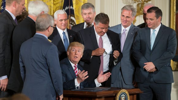 President Donald J. Trump participates in the signing ceremony of a decision memo and letter transmitting ideas on air traffic control reform to Congress, beside US Vice President Mike Pence and members of Congress in the East Room of the White House in Washington, DC on June 5.