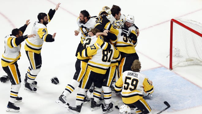 Pittsburgh Penguins players celebrate on the ice after defeating the Nashville Predators in Game 6 to clinch back-to-back Stanley Cup titles.