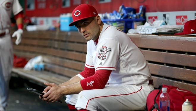 Cincinnati Reds first baseman Joey Votto (19) checks a tablet in the dugout in the third inning during a National League baseball game between the Milwaukee Brewers and the Cincinnati Reds, Monday, April 30, 2018, at Great American Ball Park in Cincinnati.