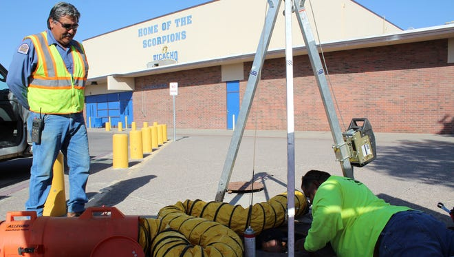 Water meter mechanic Ricardo Cordova oversees the installation of an advanced commercial water meter at Picacho Middle School.