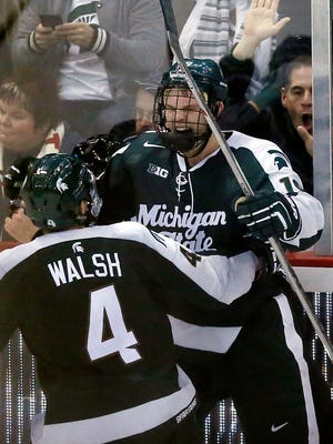 Michigan State's Matt DeBlouw, right, celebrates with Travis Walsh (4) after scoring in overtime against Michigan during a college hockey game at Joe Louis Arena on Friday, Feb. 5, 2016, in Detroit. (AP Photo/Duane Burleson)