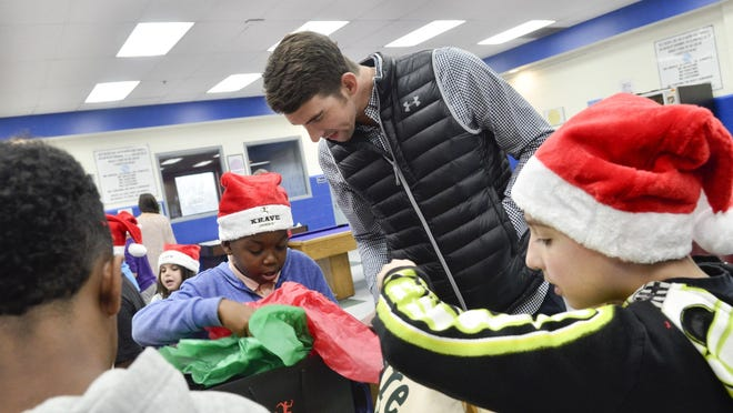 Michael Phelps hands out gift bags to children as he visits the Boys & Girls Club of Harford County in Maryland to present a check for $20,000 from the Michael Phelps Foundation and KRAVE Jerky.