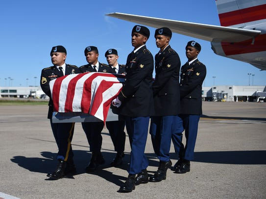 Military pallbearers from Fort Campbell carry the remains
