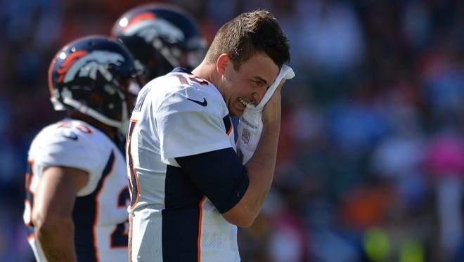 Denver Broncos quarterback Trevor Siemian (13) wipes the sweat off his face after being hit by Los Angeles Chargers outside linebacker Melvin Ingram (54) during the second quarter at StubHub Center.