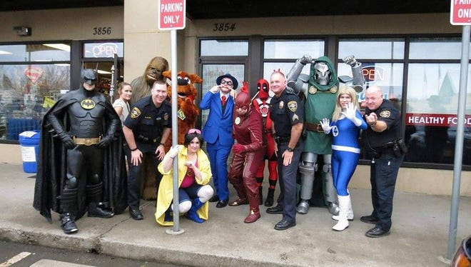 """Keizer Police pose with costumed characters at the grand reopening celebration for Tony's Kingdom of Comics & Collectibles, after receiving a call reporting """"a man in a red costume with a gun walking through the parking lot."""" It was a costumed Deadpool with prop weapon."""