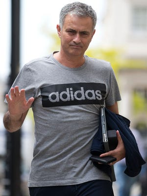 Manchester United's new manager Jose Mourinho waves as he returns to his home in central London.