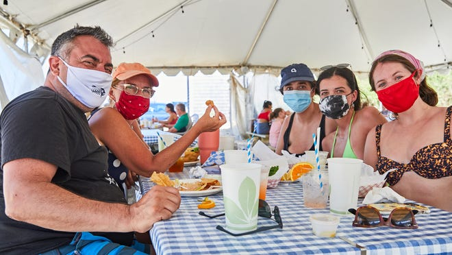 Enjoying a recent meal in the outdoor tent at The Beachcomber restaurant in Wellfleet are, from left, Gerry Filipatos, Britta Cleveland, Natalie Ware, Julia Ware, and Meryl Honig, all from New York. The popular beachside spot will be open through September for the first time in decades.