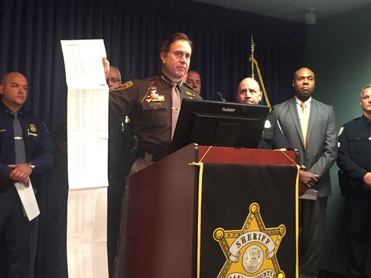 Oakland County Sheriff Michael Bouchard holds up a list of the cases where deputies have administered Narcan, a nasal spray that counteracts the effects of opioid overdoses.