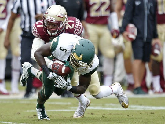 FSU's Marquez White tackles USF's Marlon Mack during