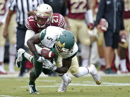 FSU's Marquez White tackles USF's Marlon Mack during a game last season. White finished the year with 25 tackles.