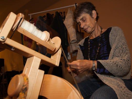 Fiber Artist Carol Eggers spins fleece from a sheep