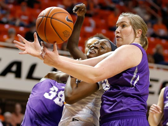 Oklahoma State's Diana Omozee, left, and Abilene Christian's Sydney Shelstead, right, vie for the ball during the first round of the Women's NIT in Stillwater, Okla., Thursday, March 16, 2017.