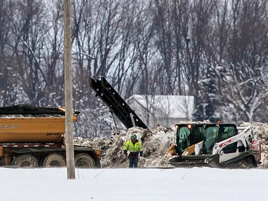 Crews work to clean up a diesel fuel spill after a pipeline owned by Magellan Midstream Partners broke near Hanlontown, Iowa on Wednesday