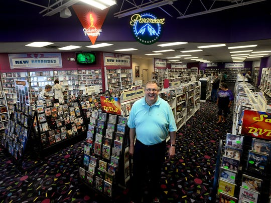 Tom Leach stands in the middle of his store, Video To Go, underneath two neon signs of Hollywood studios on Sept. 29, 2015. Video To Go, in Frandor, is closing after more than 30 years in business.