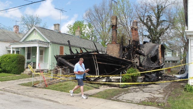 Mail carrier Kevin O'Day walks past  a home in the 300 block of E. 41st Street in Latonia, which was destroyed by an overnight fire.