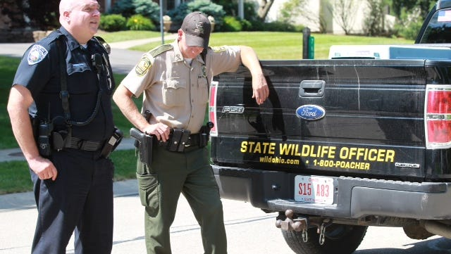 """A Montgomery police officer and Matt Roberts, Ohio state wildlife officer, stand  by Roberts' truck on Trailwind Drive where people have spotted a bear. Roberts said there is """"nothing"""" his agency can do about the bear unless it becomes a problem."""