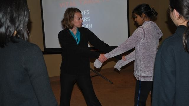 Amanda Kruse, owner and instructor at Des Moines Area Self Defense, teaches a self-defense technique to a participant during one of her classes.