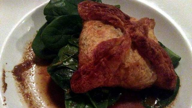 Pork Vindaloo ($18), pulled pork baked en croute with spices, served over baby spinach, raisins, and pork juices, at Hearth in Iowa City.
