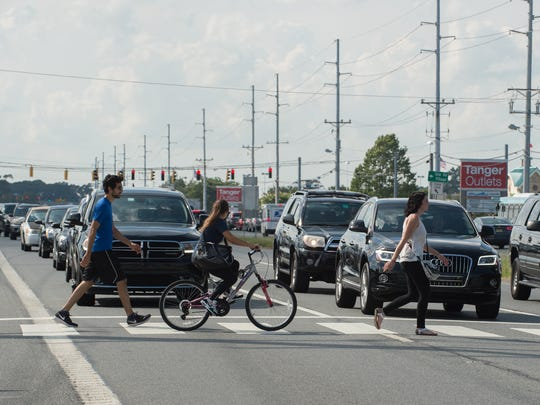 Pedestrians cross over Del. 1 in Rehoboth Beach on Tuesday. A HAWK crosswalk lets them request a brief pause in traffic.