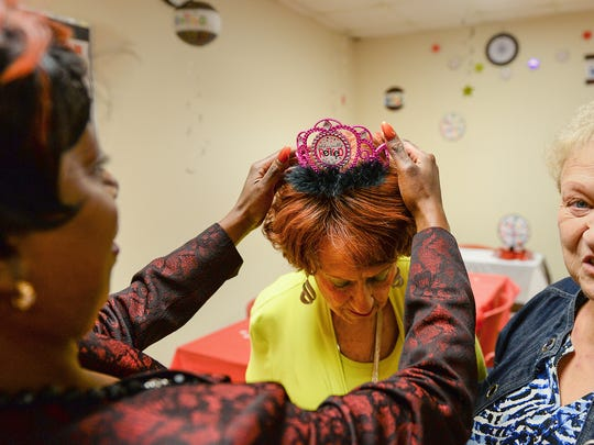 """Denise Moody-Smith puts a """"Officially Retired"""" crown on Betty Collette's head before the start of her retirement party Friday, Sept. 30, 2016 at the J.C. Penney store in the Lansing Mall. Collette, 91, is retiring after 67 years with the company."""