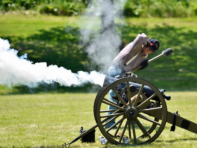 Anton Schulden protects his ears as a cannon fires