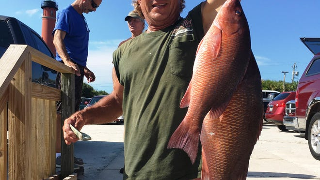 James Church, who was made famous after being struck by lightning while fishing from a Ponce Inlet jetty a few years ago, holds an 11-pound mangrove snapper caught aboard Super Critter. Church is from Port Orange.