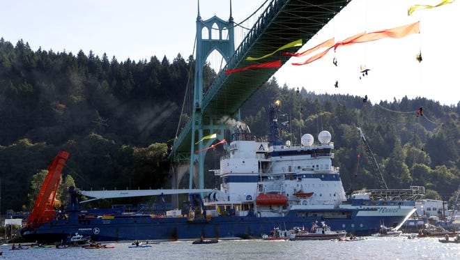 File - In this July 30, 2015 file photo, The Royal Dutch Shell PLC icebreaker Fennica heads up the Willamette River under protesters hanging from the St. Johns Bridge on its way to Alaska on July 30 in Portland, Ore.