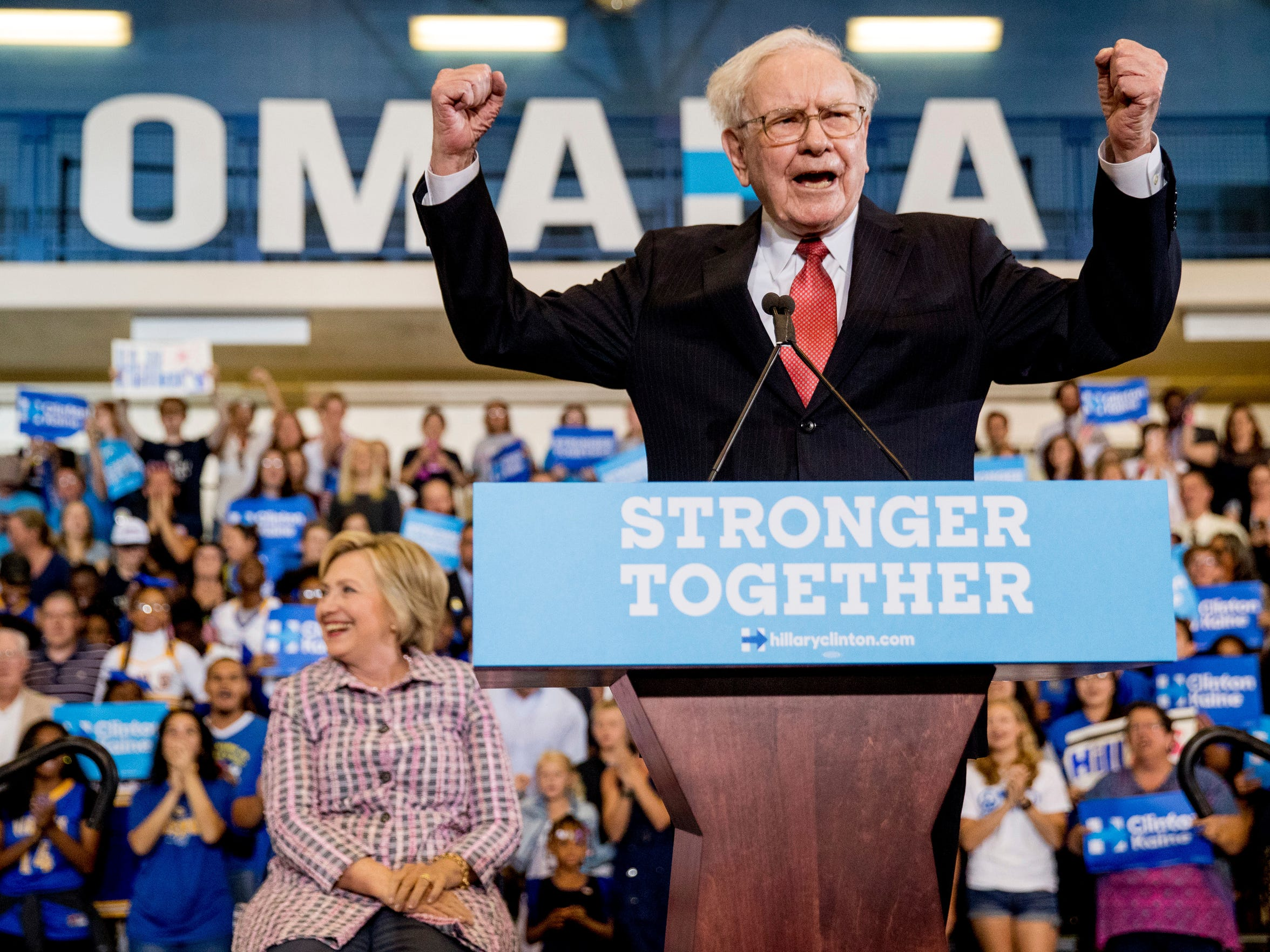 Berkshire Hathaway President and CEO Warren Buffett cheers as he and then-Democratic presidential candidate Hillary Clinton arrive at a rally at Omaha North High Magnet School in Omaha, Nebraska on Aug. 1, 2016.