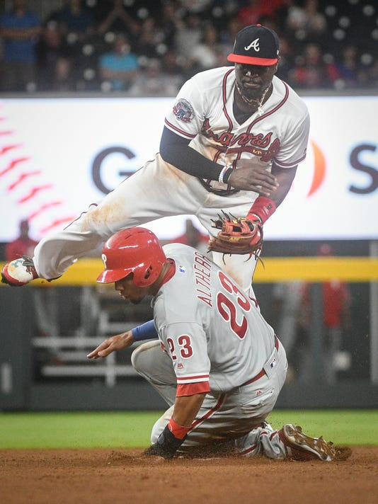 Atlanta Braves second baseman Brandon Phillips comes down on Philadelphia Phillies' Aaron Altherr (23) as he turns a double play throwing out Maikel Franco at first base during the ninth inning of a baseball game, Tuesday, June 6, 2017, in Atlanta. Philadelphia won 3-1. (AP Photo/John Amis)