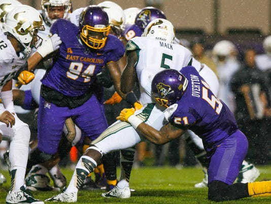 South Florida's Marlon Mack is tackled by East Carolina's Montese Overton during the first half of an NCAA football game in Greenville, N.C., on Saturday, Nov. 7, 2015. (Bayardo Caceres-Rossel/The Daily Reflector via AP)
