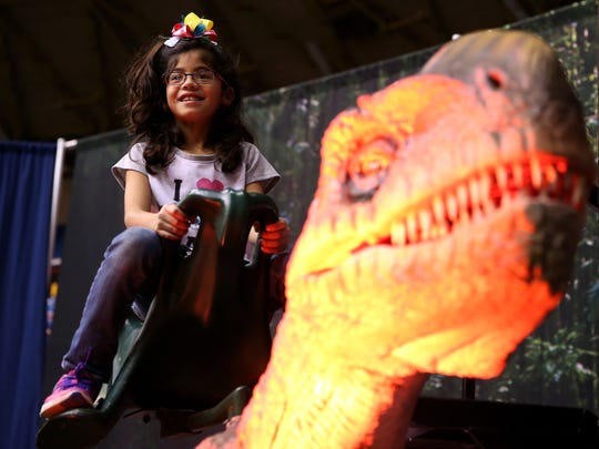 Aliana Leija takes a ride on a dinosaur during the Discover the Dinosaurs event at Foster Communications Coliseum on Saturday.