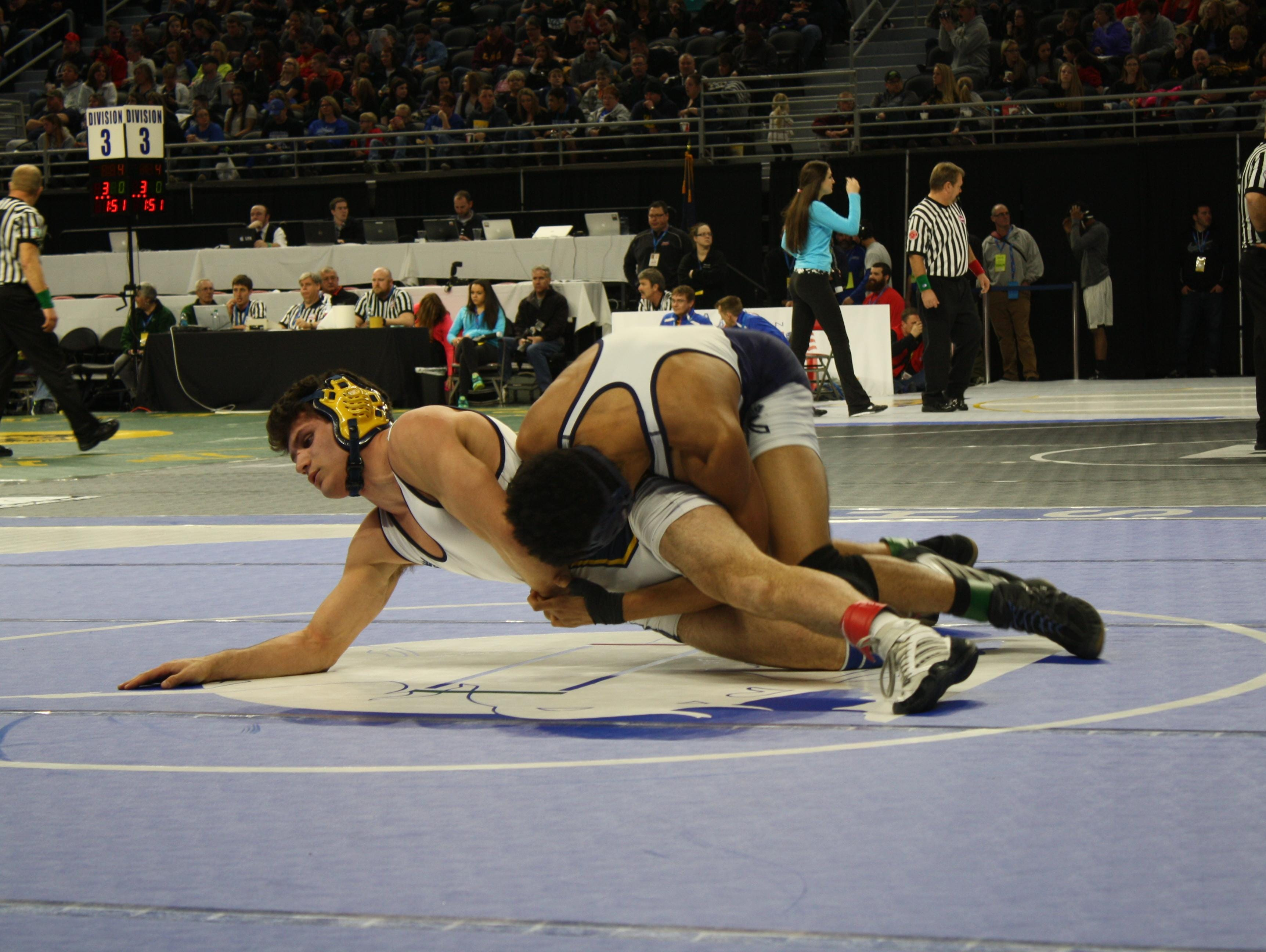 In a match at 152 pounds, Oxford's Devin Trevino tries to escape the hold of East Lansing's Malcym Carroll Thursday at the Palace of Auburn Hills.