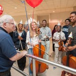 Detroit Symphony Orchestra Music Director Leonard Slatkin, left, thanks well-wishers after the surprise greeting at Metro Airport on Tuesday.