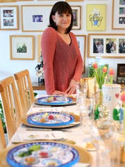 Terri Cooper, 58, of Bloomfield Township stands at the end of one of several tables she will set up for at least 30 guests for her Passover meal. Cooper has ordered paper Seder plates so that everyone has their own during their Passover meal. Cooper also condensed the Haggadah (the story told during the seder of the events that led the Jewish people from slavery) and had her family write their own.