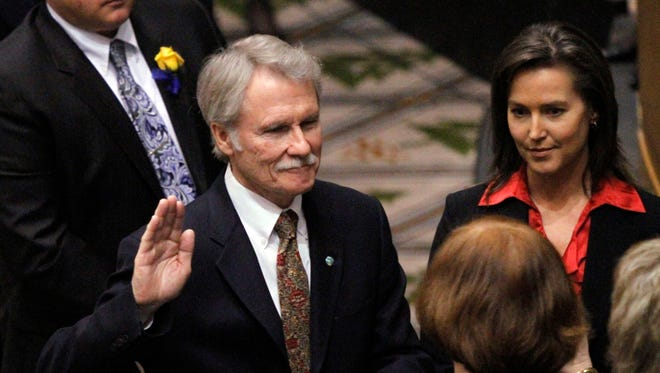 In this Jan. 10, 2011 file photo, Democrat John Kitzhaber, left, is sworn in as Oregon governor in House chambers as the 76th Oregon Legislature begins in Salem, Ore. At right is Cylvia Hayes. On Wednesday, Oct. 8, 2014, Portland's alternative weekly newspaper, the Willamette Week, reported that Kitzhaber's fiancee, Hayes, has used her role as an adviser to Kitzhaber to land contracts for her long-time job as a consultant on energy matters. (AP Photo/Don Ryan, File)