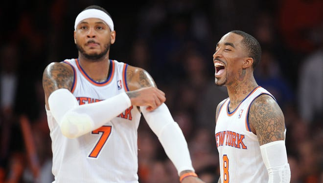 New York Knicks guard J.R. Smith (8) and forward Carmelo Anthony (7) celebrate their blowout victory of the Brooklyn Nets at Madison Square Garden.