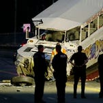 """Police officers and other officials watch as a """"Ride the Ducks"""" tourist vehicle is loaded onto a flatbed tow truck in the late evening Thursday, Sept. 24, 2015, after it was involved in a fatal crash with a charter passenger bus earlier in the day in Seattle. (AP Photo/Ted S. Warren)"""