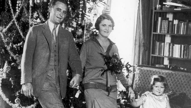 Zelda Fitzgerald holds hands with her husband F. Scott and daughter Frances in front of their Christmas tree in 1925.