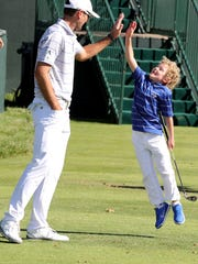 Jason Allred 'high fives' his five year old son Zane Aldred on the driving range during the a practice round prior to the 2016 U.S.Open in Oakmont, Pennsylvania.