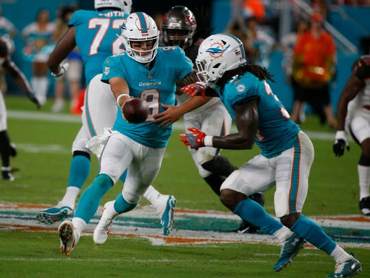 Miami Dolphins quarterback David Fales (9) hands the ball to running back Senorise Perry (34), during the first half of an NFL preseason football game against the Tampa Bay Buccaneers, Thursday, Aug. 9, 2018, in Miami Gardens, Fla. (AP Photo/Wilfredo Lee)