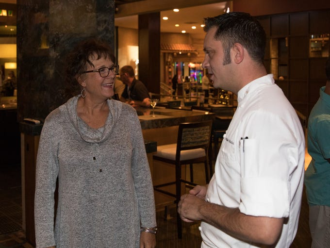 Chef Michael Mahoney talks with guests during a cooking